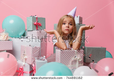 stock photo portrait of a sad pretty little girl in a birthday hat sitting in a pile of present boxes and 744691162