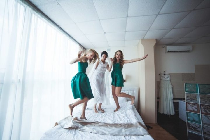 cheerful women jumping on bed before wedding