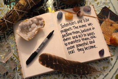 cute journal with a sharpie some rocks and a feath